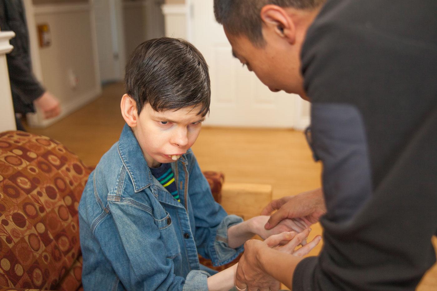 L'interprète tactile sourit en aidant un homme à peindre un objet artisanal à la table de la cuisine.