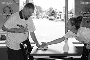 Intervenor and man supported stand on opposite ends of a table in a restaurant where the man has a supported volunteer placement. The intervenor places her hand over the man's, assisting him with wiping the table.